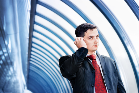 A successful businessman with the documents talking by mobile phone