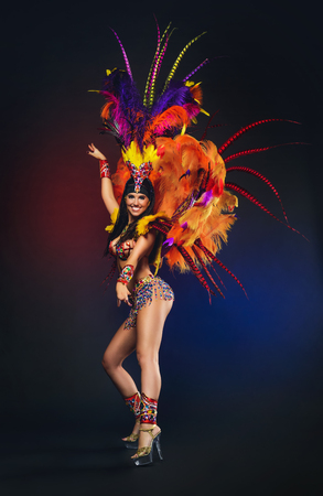 Cute young girl in bright colorful carnival costume on dark background Stok Fotoğraf