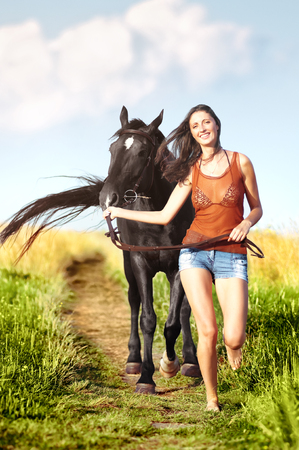 Young beautiful girl walking with a horse on the field
