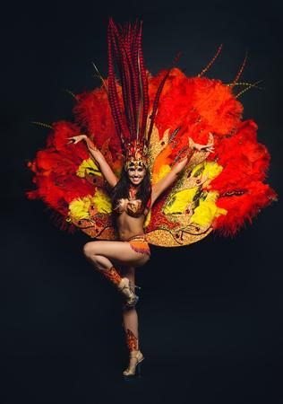 Cute young girl in bright colorful carnival costume on dark background Foto de archivo