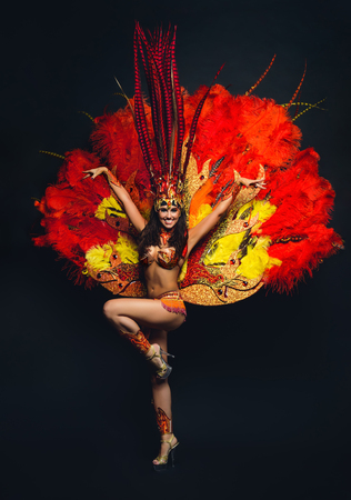 Cute young girl in bright colorful carnival costume on dark background Archivio Fotografico