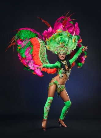 sexy girl dance: Cute young girl in bright colorful carnival costume on dark background Stock Photo