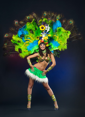 Cute young girl in green carnival costume on dark background