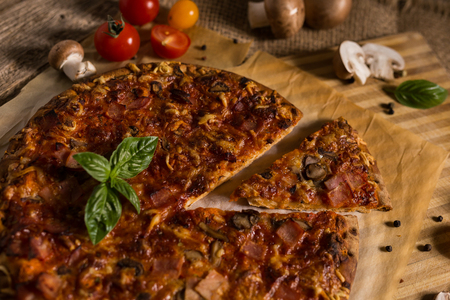 Pizza with salami, mushroom and vegetables on the old rustic wood table