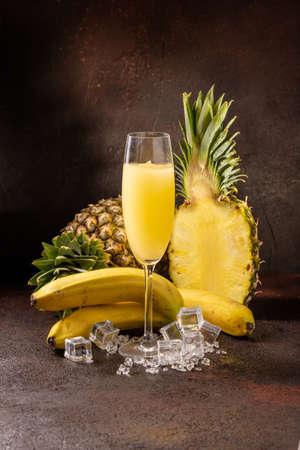 Delicious cold refreshing ananas smoothie drink in cocktail glass with banana Zdjęcie Seryjne