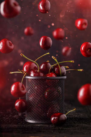Flying or levitated cherries on a dark background with steam or water particles
