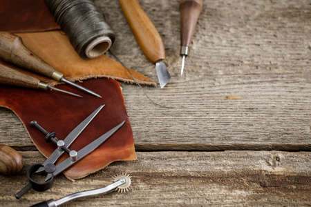 Leather craft tools on the old wood table in a shed. Leather craftsman workspace. Grounge dark wood texture background.