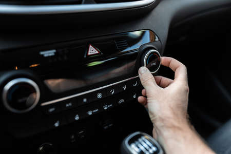 Young man adjusting the climate of the car with air conditioner or climatic system's controller. Interior view of a car. User and car concept. Foto de archivo