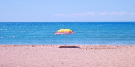 White sandy beach, sea and blue sky with umbrella