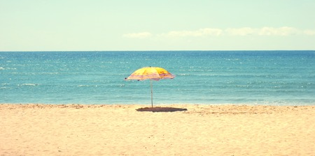 White sandy beach and blue sky with a yellow umbrella
