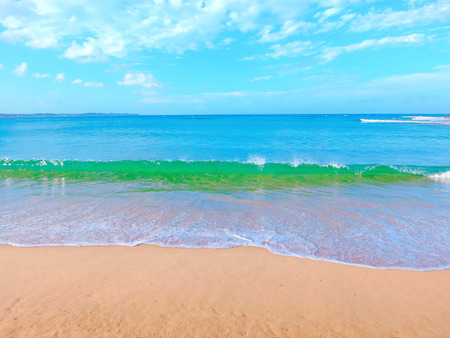 White sandy beach, sea, wave and blue sky with clouds