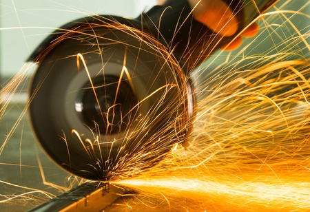 warehouse worker: Red hot sparks at grinding steel material