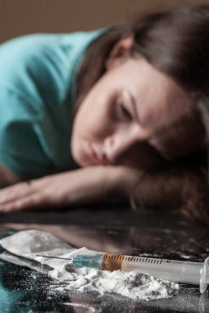 Young woman and syringe with heroin on table Stock Photo