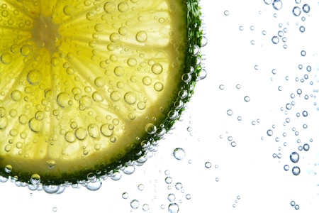 fresh lime slice in water with bubbles