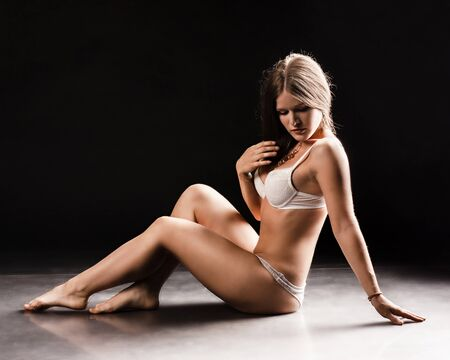 nude wet: Young sexy woman sit on the floor. studio photo.