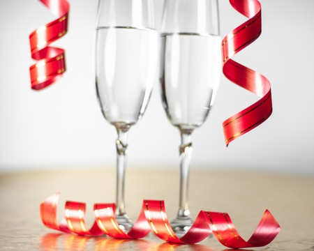 two champagne glasses with a red ribbon photo