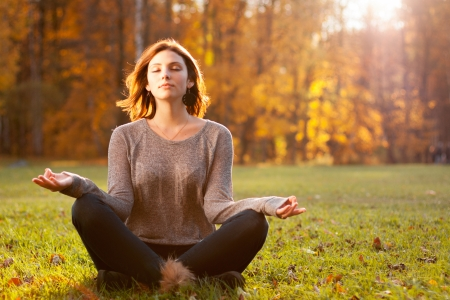 mujer meditando: Hermosa joven meditando en el parque otoño