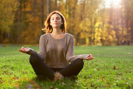 wellness woman: Beautiful young girl meditating in autumn park