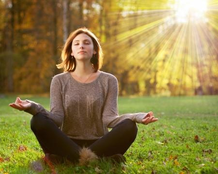 Het mooie jonge meisje mediteren in de herfst park Stockfoto - 24564720