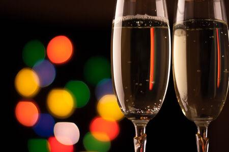 brindisi spumante: due bicchieri di champagne tostatura contro bokeh luci