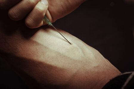 drug overdose: Hand with heroin syringe. Close-up photo. Stock Photo