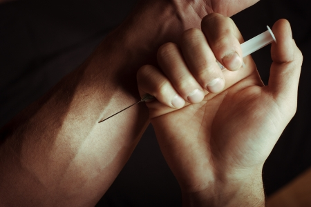 narcotism: Hand with heroin syringe. Close-up photo. Stock Photo