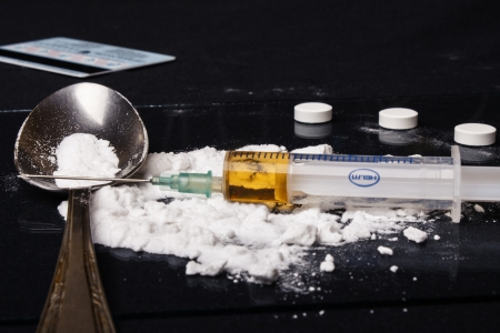 Drug syringe and cooked heroin on spoon