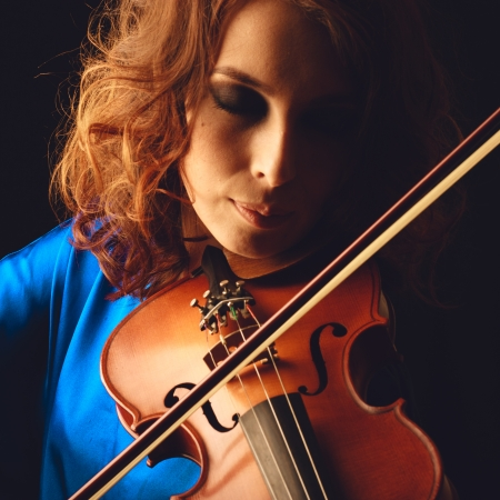 Violin playing violinist musician. Woman classical musical instrument player on black photo