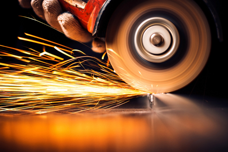 Worker cutting metal with grinder. Sparks while grinding iron Banco de Imagens - 26452080