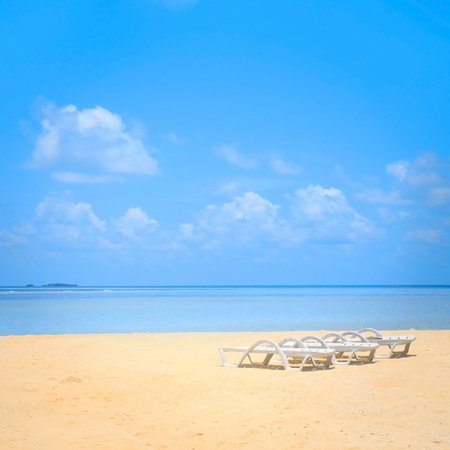 Beach chairs on the white sand beach with beautiful cloudy blue sky photo