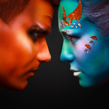 with orange and white body: two contrasts. fire and water. the photo in a profile of the man and the woman. body art