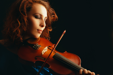 Female violinist playing on black photo
