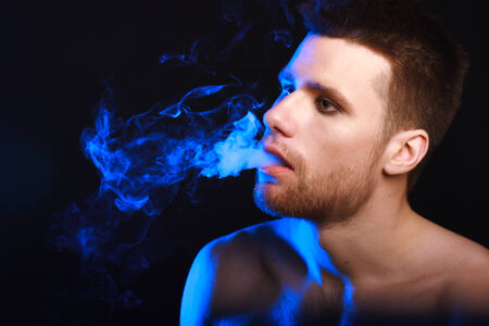 Close up portrait of young man smoking cigarette photo