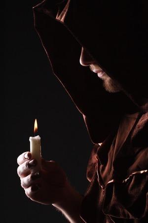 tovenaar in zwarte cape met kaars