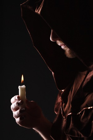wizard in black cape with candle Stock Photo