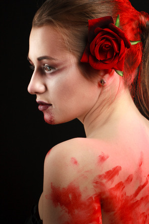 portrait of beautiful gothic girl with rose and blood. blood photo
