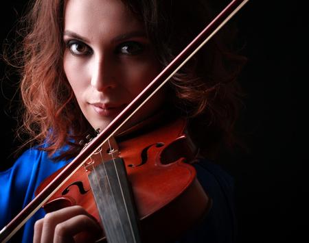 violins: Violins performer hands playing on dark background.