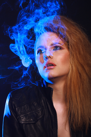 Woman with Cigarette Exhaling Smoke  on a Dark Background Stock Photo