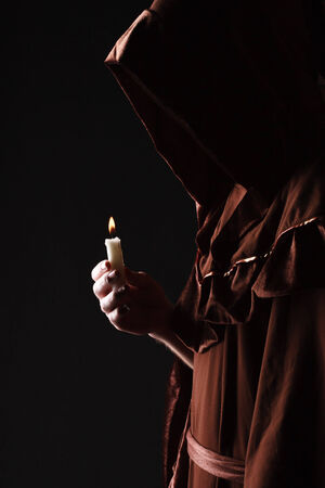 wizard in black cape with candle photo