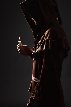 cleric: wizard in black cape with candle Stock Photo