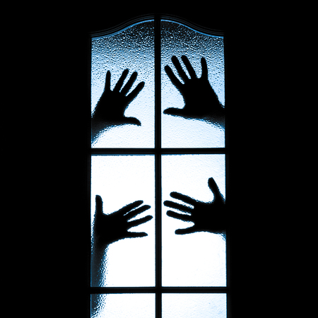 Scary hands behind glass window photo
