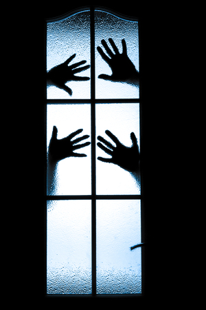 Scary sets of hands behind window photo