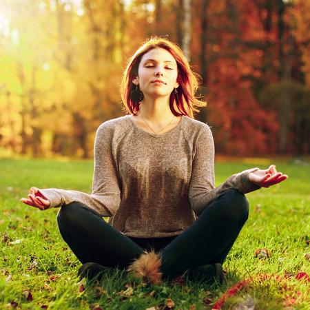 Het mooie jonge meisje mediteren in de herfst park