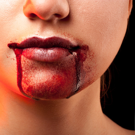Closeup of Red lips of a young girl, with blood flowing by. photo