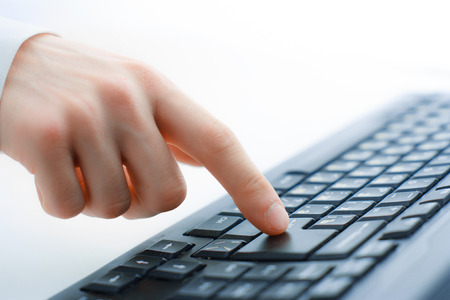 Close-up of typing male hands on keyboard photo