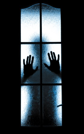 self harm: Scared boy behind glass door showing one hand