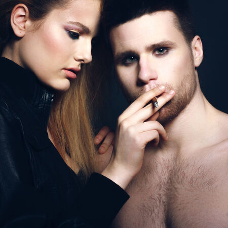 woman leaning on her man looking at the camera while he is smoking his cigarette