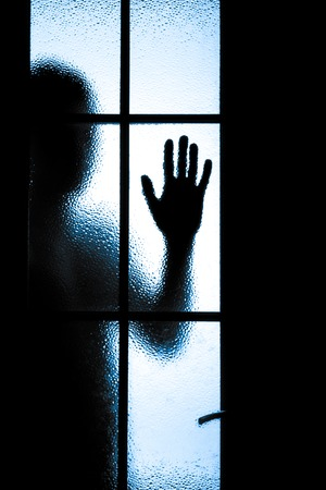 1 つの手を示すガラスのドアの後ろに少年が怖い 写真素材