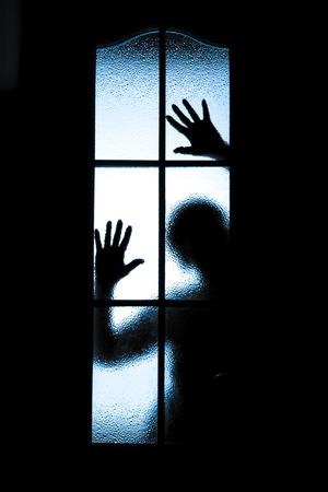 Scared boy behind glass door showing one hand photo