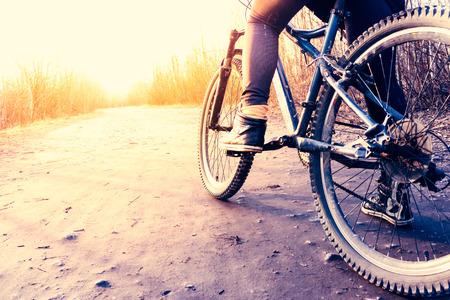 lage hoek weergave van fietser mountainbike op rotsachtig pad bij zonsopgang
